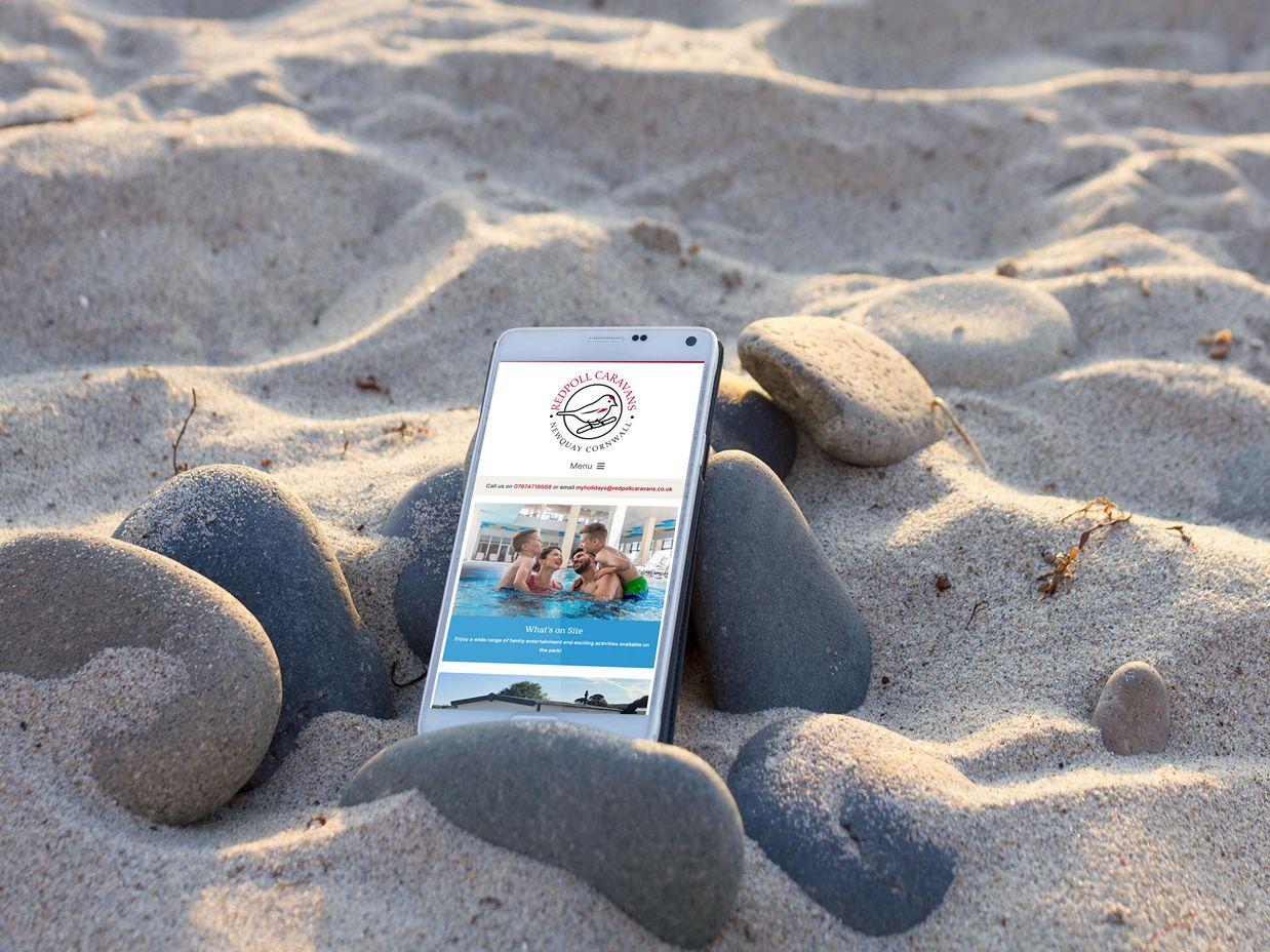 Smartphone on beach sand displaying website