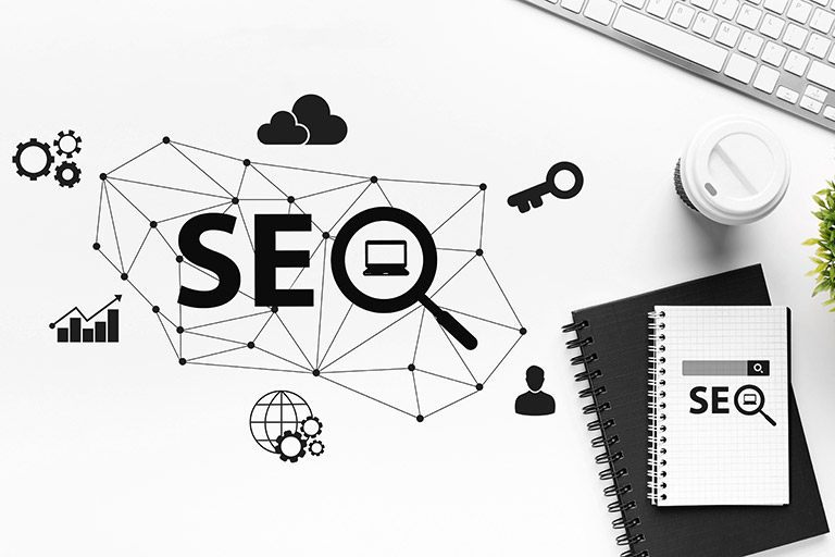 SEO optimisation concept with web icons over white office table background with keyboard. internet content promotion and search engine optimisation